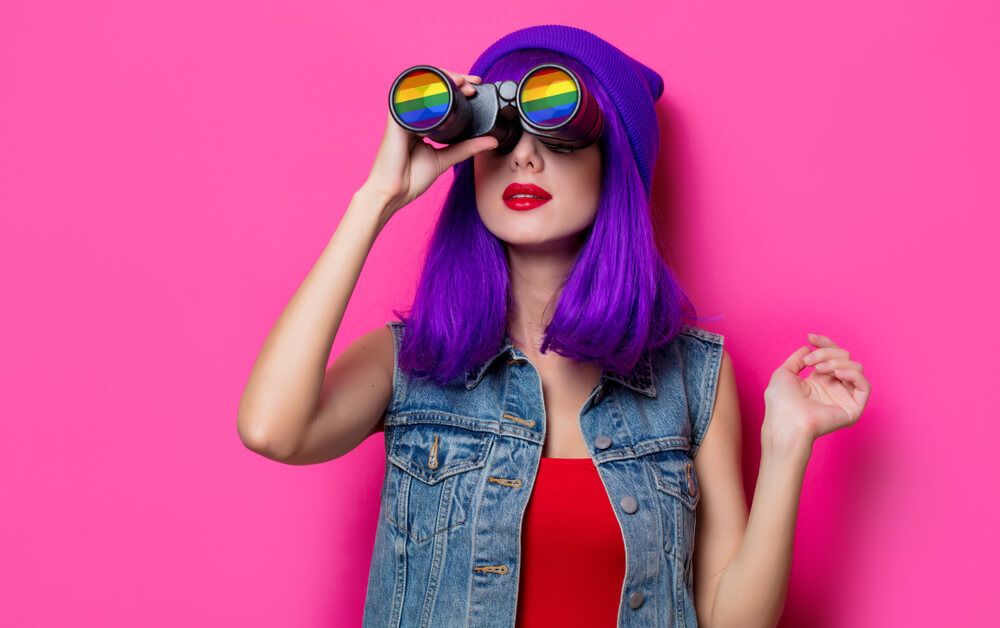 Woman with purple hair and beannie looking far away with a rainbow lens telescope