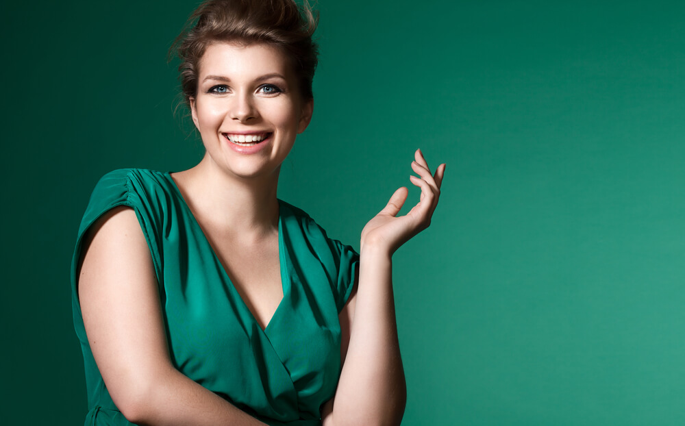 Confident curvy woman dressed in green, smiling