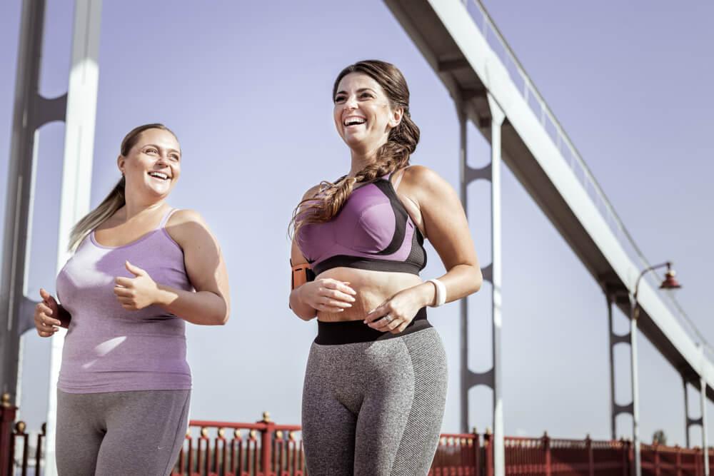 Two curvy women in their sportswear, running under the bridge