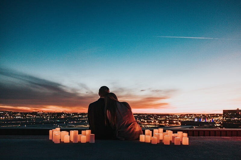 Couple sitting on a roof with candles in the evening