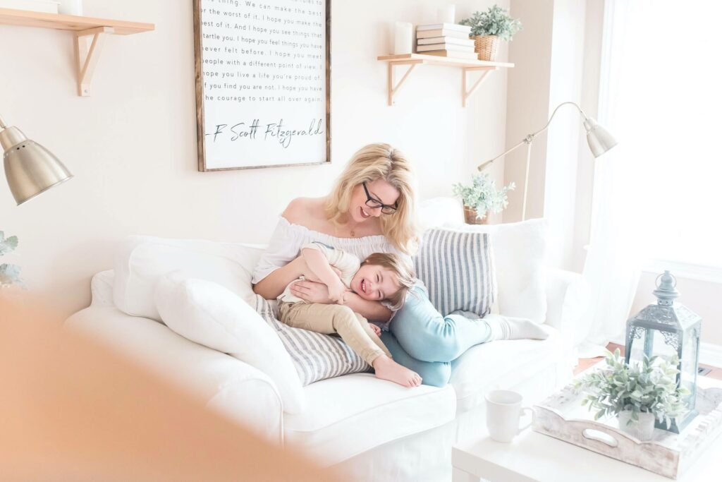 Blonde mother playing with her son on a sofa