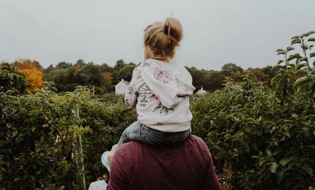 Singles dad with his daughter over his shoulders walking among trees