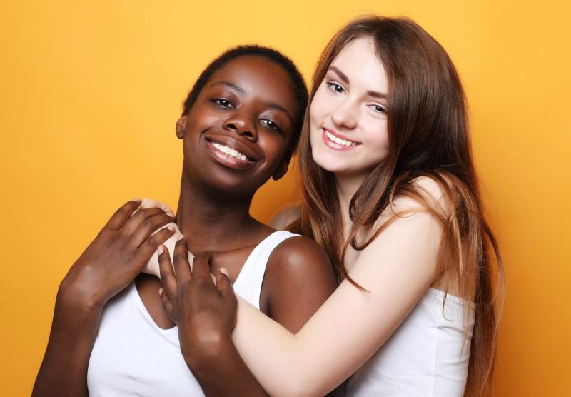 lesbian interracial couple smiling into the camera while hugging fondly