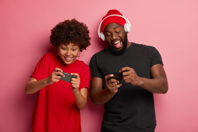 geek couple challenging each other in a smartphone game