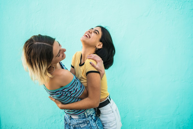 lesbian girl lifts her girlfriend up in the air