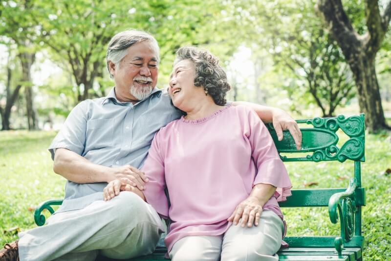 cute senior couple laughing while sitting on a bench in the park