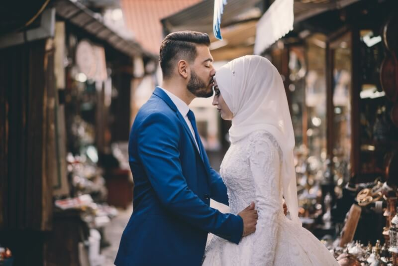 newly-wed muslim husband kisses bride on forehead