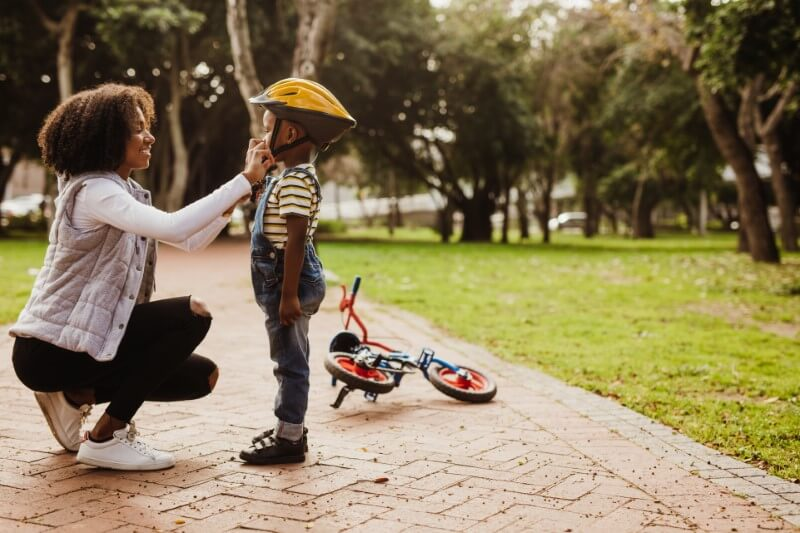 single mom helps her son with his helmet while he learns how to drive a bike