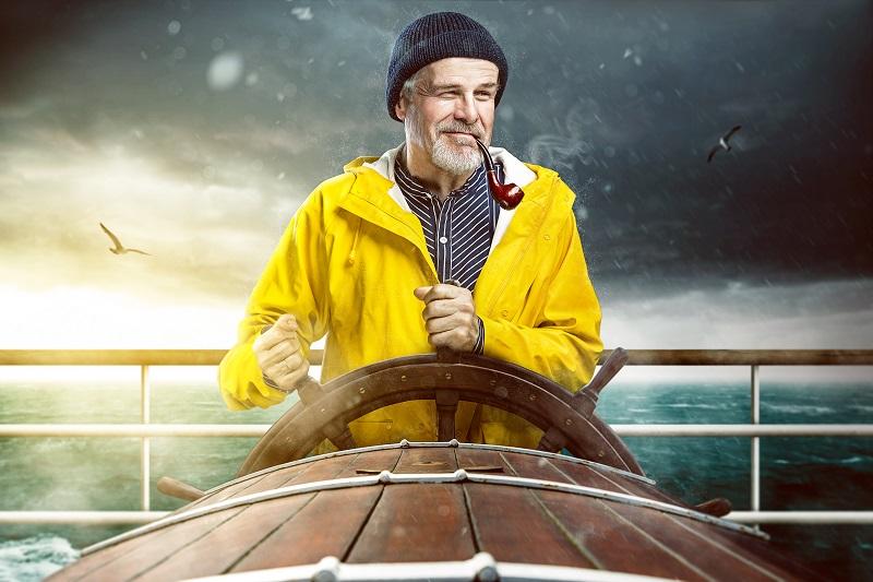 Charming sea captain steering a boat at sea