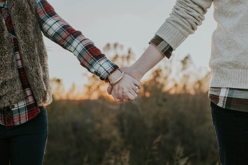 two people holding hands outside