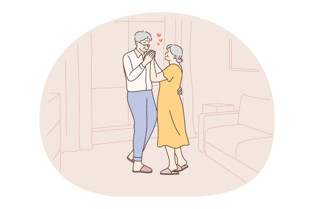 senior couple dance in their living room